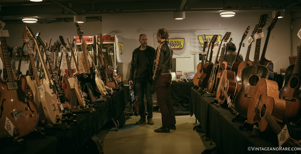 Which one to buy? Gentlemen going over stuff at the booth of V&R seller, Jam Guitars